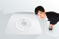 Serious businesswoman bending against retro telephone Royalty Free Stock Photography