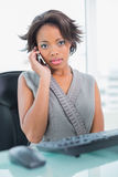 Serious businesswoman calling on phone while looking at camera Stock Photo