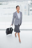 Serious businesswoman carrying her suitcase Stock Photos