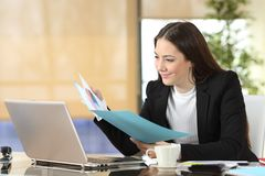 Serious businesswoman checking informs at office. Serious businesswoman checking paper informs sitting at office stock photo