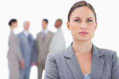 Serious businesswoman with co-workers behind her Stock Image