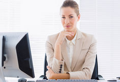 Serious businesswoman with computer at office desk Stock Image