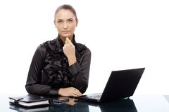 Serious businesswoman at desk. Serious businesswoman in fancy shirt sitting at desk, looking confident and strict, cutout on white Stock Photo