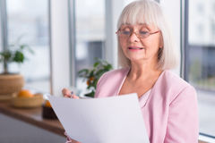 Serious businesswoman examining a document Stock Photography