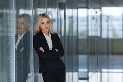 Serious businesswoman with folded arms in office. Stock Images