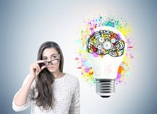 Serious businesswoman in glasses, cog brain, bulb Royalty Free Stock Photography