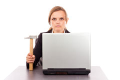 Serious businesswoman with a hammer sitting at office desk. Isolated on white stock photo