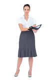Serious businesswoman holding her datebook. On white background Stock Photography