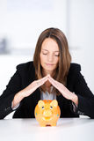 Serious Businesswoman Joining Fingers Above Piggy Bank Royalty Free Stock Photos