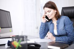 Serious businesswoman listening to a phone call. Serious businesswoman listening to a telephonephone call at her desk reading peperwork in front of her as she Stock Photo