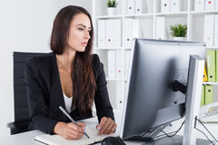 Serious businesswoman with long hair taking notes Royalty Free Stock Photos