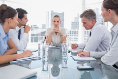 Serious businesswoman looking at camera with colleagues around Royalty Free Stock Photo
