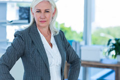 Serious businesswoman looking at camera with hands on hips Royalty Free Stock Photos