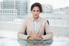 Serious businesswoman looking at camera at her desk Royalty Free Stock Photos
