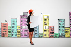 Serious businesswoman. In orange hardhat with blueprint looking up over background with variegated drawing houses Royalty Free Stock Image