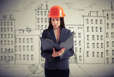 Serious businesswoman over drawing street. Serious businesswoman in orange hardhat  with black folder over drawing street Royalty Free Stock Image