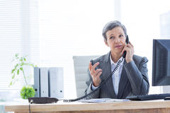 Serious businesswoman phoning and using computer Royalty Free Stock Image