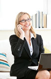 Serious businesswoman phoning and using laptop Stock Photos