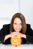 Serious Businesswoman With Piggy Bank At Desk Royalty Free Stock Photo