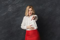 Serious businesswoman pointing on camera. Confident businesswoman pointing on camera. Woman gesturing with her finger aside, gray studio background, copy space Stock Images