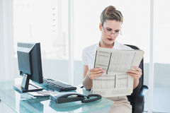 Serious businesswoman reading newspaper Stock Images
