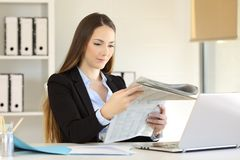 Serious businesswoman reading a newspaper at office. Serious businesswoman reading a newspaper sitting in a desk at office Stock Photo