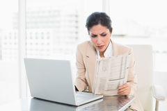Serious businesswoman reading newspaper while working on laptop Stock Images