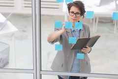 Workflow. Serious businesswoman reading working reminders on notepapers on board Royalty Free Stock Photos