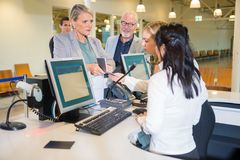Serious Businesswoman Showing Passport To Staff At Airport. Serious businesswoman showing passport to female staff at airport check-in Stock Image