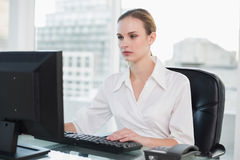Serious businesswoman sitting at desk Stock Photos