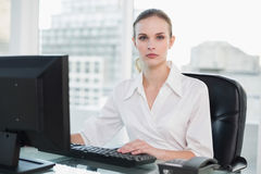 Serious businesswoman sitting at desk looking at camera Stock Photo