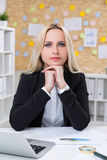 Serious businesswoman. Sitting at desk in office Royalty Free Stock Photography