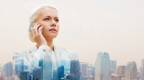 Serious businesswoman with smartphone in city Stock Images