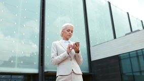 Serious businesswoman with smartphone outdoors Royalty Free Stock Image