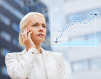 Serious businesswoman with smartphone outdoors Stock Photos