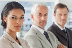 Serious businesswoman smiling with colleagues behind Stock Photography