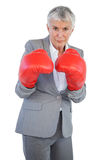 Serious businesswoman standing with her boxing gloves Royalty Free Stock Photos