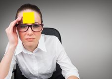 Serious businesswoman with sticky note on her forehead. Against grey background Royalty Free Stock Images
