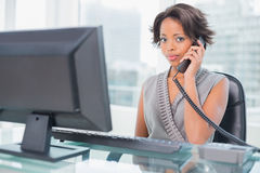 Serious businesswoman talking on phone while looking at camera Stock Photos
