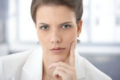 Serious businesswoman thinking. Closeup facial portrait of serious businesswoman thinking, looking at camera Stock Image