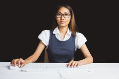 Serious businesswoman using a computer. On black background Stock Photography