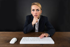 Serious Businesswoman Using Computer Mouse And Keyboard On Desk. Portrait of serious young businesswoman using computer mouse and keyboard on desk over black Stock Photo