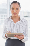 Serious businesswoman using her tablet pc Stock Images