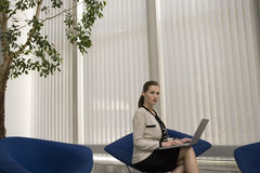 Serious Businesswoman Using Laptop In Office Lobby Royalty Free Stock Image
