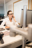 Serious businesswoman using mobile phone while sitting at desk. In office Royalty Free Stock Image