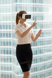 Serious businesswoman in VR headset trying virtual reality 3d to. Ur, interacting with virtual interface to make conference call, watching 360 degrees video royalty free stock photo