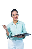 Serious businesswoman wearing glasses taking notes in her clipboard Royalty Free Stock Image