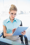 Serious businesswoman wearing glasses using tablet Royalty Free Stock Photography