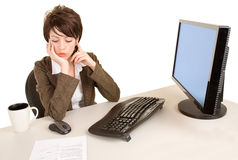 Serious Businesswoman Working at her Desk. An attractive serious businesswoman is working at her desk Royalty Free Stock Photos