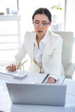 Serious businesswoman working at her desk. In her office stock images